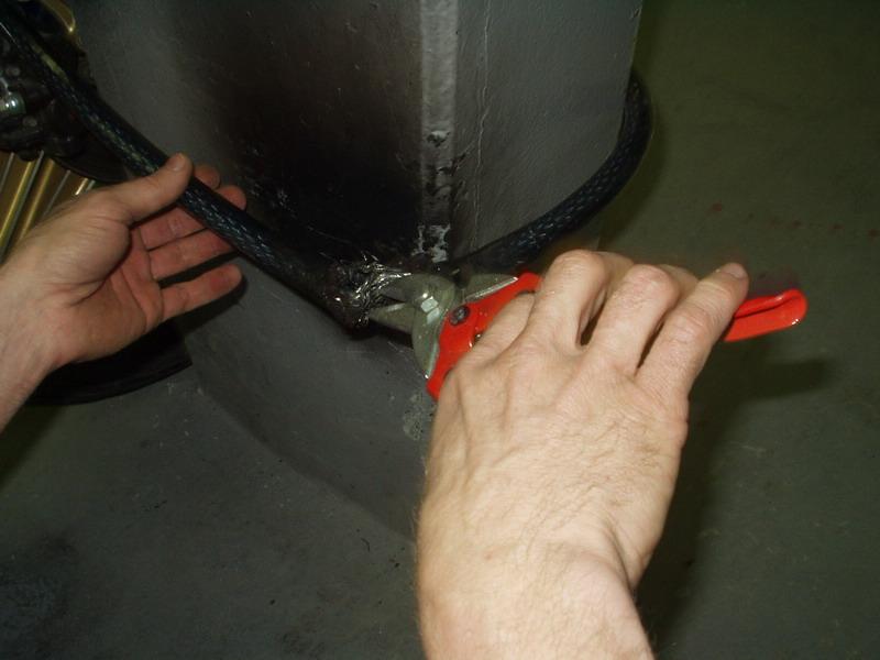 Zámok č. 2, inštalácia na prednom kolese: po piatich minútach sa podarilo zdolať asi polovicu spletaného lana (nožnice na plech použité iba ilustračne)